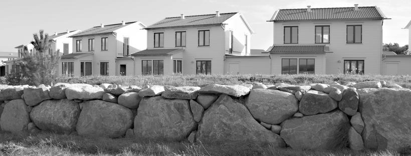 Bild på bostäder i radhusform bakom en vacker stenmur
