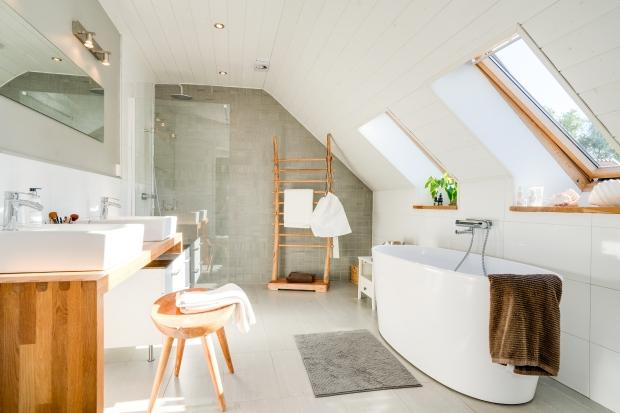 Lyxigt badrum med hörndusch, designbadkar, dubbla handfat, träpanel och kakel