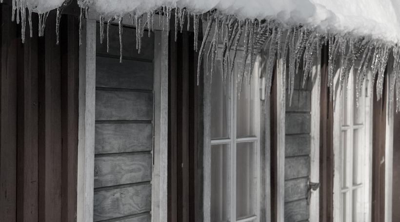 bild på istappar över dörr och fönster på stuga