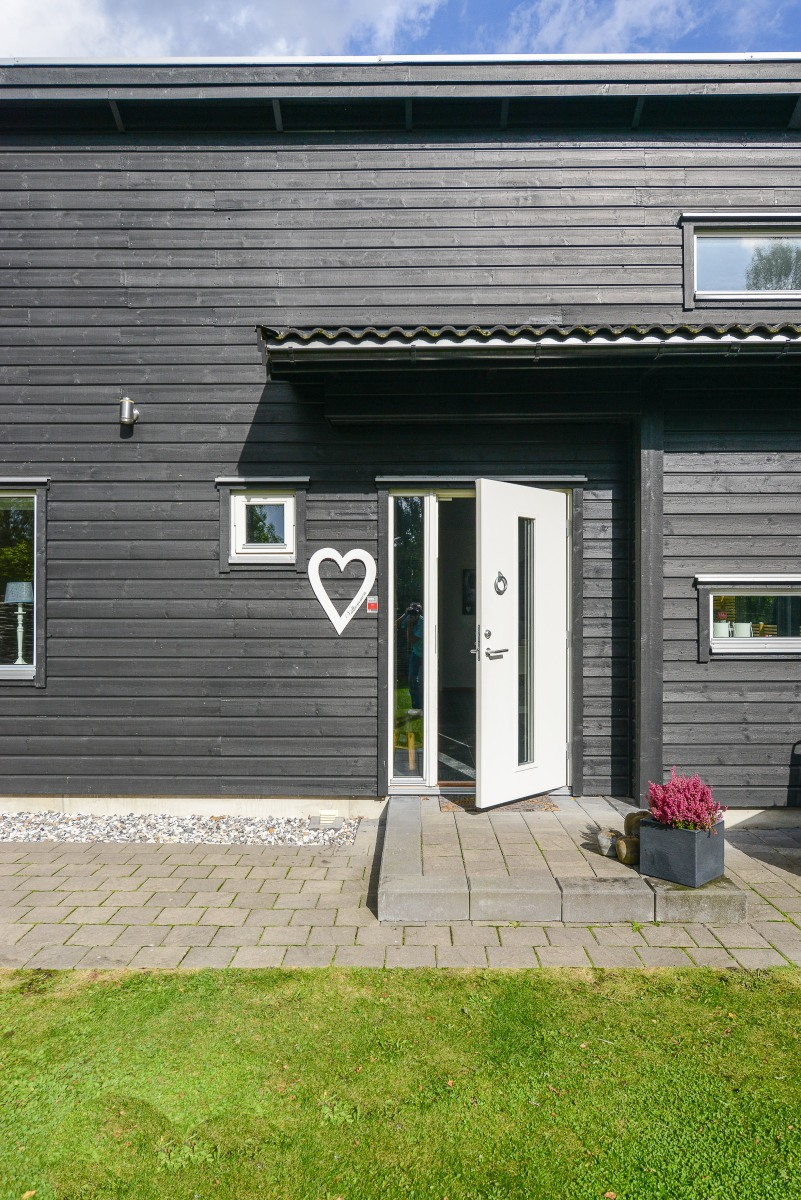 Måla huset? Svart hus med liggande panel och vit entrédörr