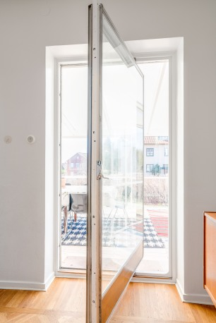 Dörren sitter, liksom husets fönster, i en alukassett och svänger runt sin egen axel.