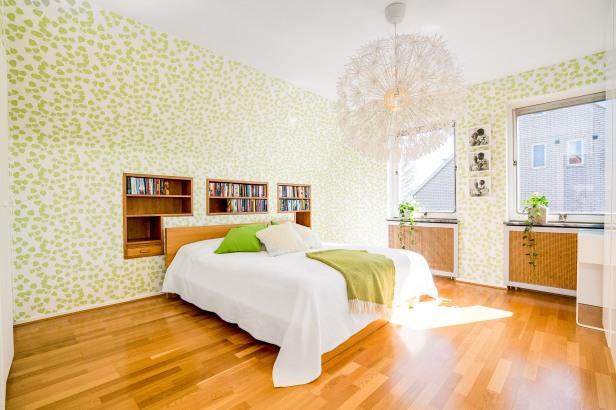 Inbyggda hyllor i sovrum med skir tapet med gröna blad