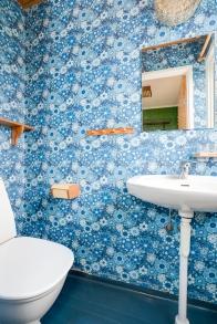 En blå gäst-wc för dig som gillar retro, blommig tapet i blått och blå matta