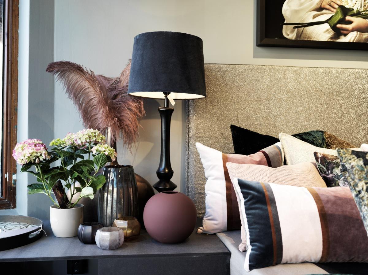 Kuddar, sänggavel och nattygsbord med lampa och prydnader. Foto: Anders Sällström Photography