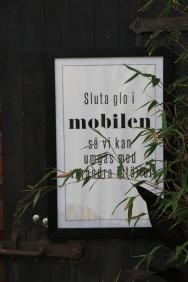 Sluta glo i mobilen så vi kan umgås med varandra istället. På en skylt i caféet.