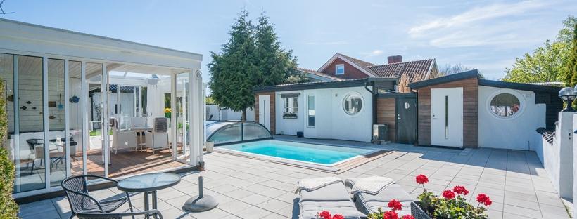 Inramad poolmiljö med stor stensatt terrass
